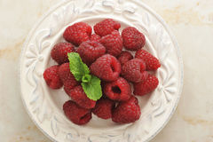 Fresh raspberries on a plate on a marble background Stock Photos