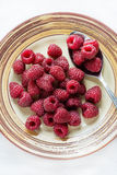 Fresh raspberries on plate over light background. Overhead Royalty Free Stock Images