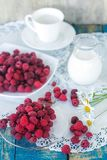 Fresh raspberries on a plate, a white cup, chamomile and a jug of milk on a blue wooden background in a rustic style. Still life. Selective focus Royalty Free Stock Photo