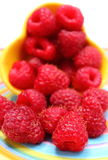 Fresh raspberries pouring out of yellow bowl. Closeup of fresh raspberries pouring out of yellow bowl on colorful plate Stock Photos