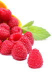 Fresh raspberries pouring out of yellow bowl. White background Stock Images