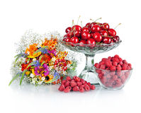 Fresh raspberries, red cherries  and flowers. Fresh raspberries, red cherries in glass bowl and beautiful colorful flowers Stock Photography