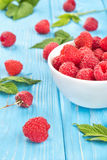 Fresh raspberries. Fresh red raspberry with a full bowl of berries and leaves scattered on a wooden background Stock Images