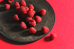 Fresh raspberries on rustic black plate. Red background. From above Stock Images