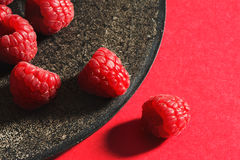 Fresh raspberries on rustic black plate. Red background. From above Stock Photography