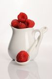 Fresh raspberries scattered on white background. Small jug with fresh raspberry by a breakfast Stock Photography