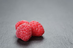 Fresh raspberries on slate surface closeup. Photo Royalty Free Stock Images