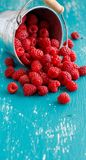 Fresh raspberries in a bucket. Fresh raspberries in a small metal bucket on a blue turquoise  background Stock Photos