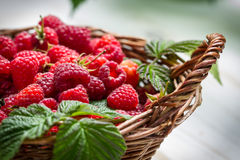 Fresh raspberries in a small wicker basket. On old table Royalty Free Stock Image
