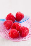 Fresh raspberries and spoon. Closeup of bunch of fresh red raspberries with blue plastic spoon resting on decorative pink mat on light surface Royalty Free Stock Image
