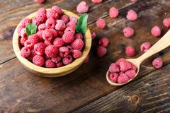 Fresh raspberries in a spoon. Raw fresh raspberries in a spoon on a wooden background, well visible texture of berries, space for text Stock Photo