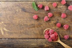 Fresh raspberries in a spoon. Raw fresh raspberries in a spoon on a wooden background, well visible texture of berries, space for text Royalty Free Stock Image