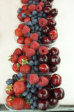 Fresh , raspberries, strawberries, cherries, blueberries in the box on the market Stock Photo