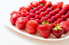 Fresh raspberries and strawberries on a white plate. Isolated on a white background Royalty Free Stock Photos