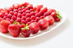 Fresh raspberries and strawberries on a white plate. Isolated on a white background Royalty Free Stock Image