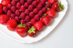 Fresh raspberries and strawberries on a white plate. On a white background Stock Photos
