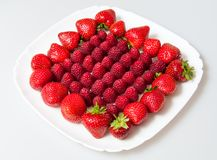 Fresh raspberries and strawberries on a white plate. Isolated on a white background Stock Photography