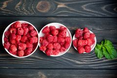 Fresh raspberries in three white plates with peppermint mints on. Fresh raspberries in three white plates with mint Royalty Free Stock Image