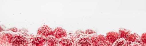 Fresh raspberries in water wiht air bubbles. Close-up photo Stock Image