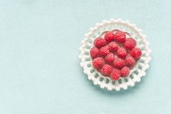 Fresh raspberries in white bowl on light turquoise background, top view with copy space stock images