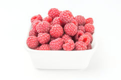 Fresh raspberries in a white bowl. Ripe sweet red raspberries fruit in a plate  on white background cutout Royalty Free Stock Photo