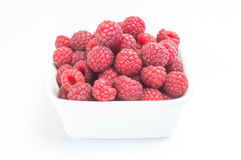Fresh raspberries in a white bowl. Ripe sweet red raspberries fruit in a plate on a white background. Healthy raw food Stock Photography