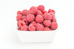 Fresh raspberries in a white bowl. Ripe sweet red raspberries fruit in a plate isolated on white background cutout Royalty Free Stock Photos