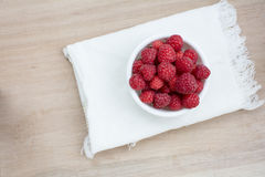 Fresh Raspberries in white bowl with white napkin. On blur wooden board background Stock Images