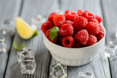 Fresh raspberries in a white bowl. On a wooden table Stock Images