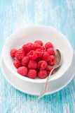 Fresh raspberries in a white ceramic bowl with metal spoon Royalty Free Stock Photos
