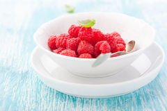 Fresh raspberries in a white ceramic bowl with metal spoon Stock Photos