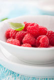 Fresh raspberries in a white ceramic bowl with metal spoon Royalty Free Stock Photography