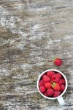 Fresh raspberries in white cup. On wooden rustic table. Top view. Copy space background Royalty Free Stock Image