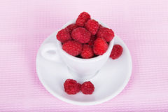 Fresh raspberries in a white cup. On a pink background Stock Photos