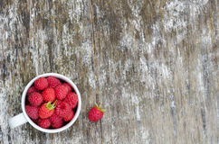 Fresh raspberries in white cup. On wooden rustic table. Top view. Copy space background Stock Images