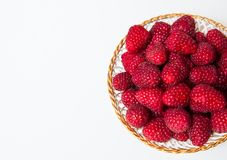 Fresh raspberries on a white plate. Isolated on a white background Royalty Free Stock Image