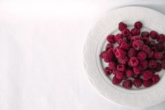 Fresh raspberries in a white plate. Red fresh raspberries in a plate on white tablecloth background. Top view with copy space Stock Photos
