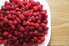 Fresh raspberries in a white plate. On a wooden table Royalty Free Stock Photo