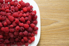 Fresh raspberries in a white plate on a wooden table. Fresh raspberries in a white plate. Stock Photo Stock Photography