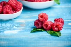 Fresh raspberries in white plates with mint mints on the table. Fresh raspberries in white plates with mint Royalty Free Stock Photography