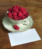 Fresh raspberries and white porcelain set. Fresh ripe raspberries and white porcelain set cup and saucer Royalty Free Stock Photo