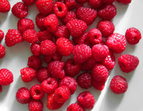 Fresh raspberries on white table. Fresh raspberries lying on a white table Royalty Free Stock Image