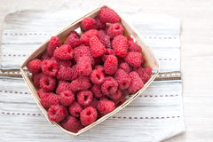 Fresh raspberries in a wicker basket, top view. Fresh raspberries in a wicker basket on a village tablecloth, top view. Healthy helpful food Stock Photo