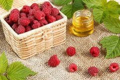 Fresh raspberries in a wicker box and honey, green leaves Royalty Free Stock Photos