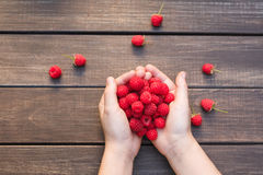 Fresh raspberries in woman`s hands on wood background. Handful of fresh raspberries in woman`s hands on brown rustic wood background. Harvest of healthy food Stock Photo