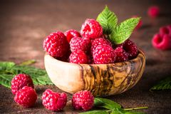 Fresh raspberries in wooden bowl. Fresh raspberries in wooden bowl on dark stone table. Close up Royalty Free Stock Photos