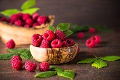 Fresh raspberries in wooden bowl. Fresh raspberries in wooden bowl on dark stone table. Close up Stock Photos