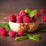 Fresh raspberries in wooden bowl. Fresh raspberries in wooden bowl on dark stone table. Close up Royalty Free Stock Photography
