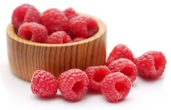 Fresh Raspberries in a wooden bowl. Over white background Stock Photos