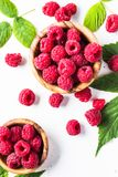 Fresh raspberries in wooden bowl on white table. Top view Stock Photo